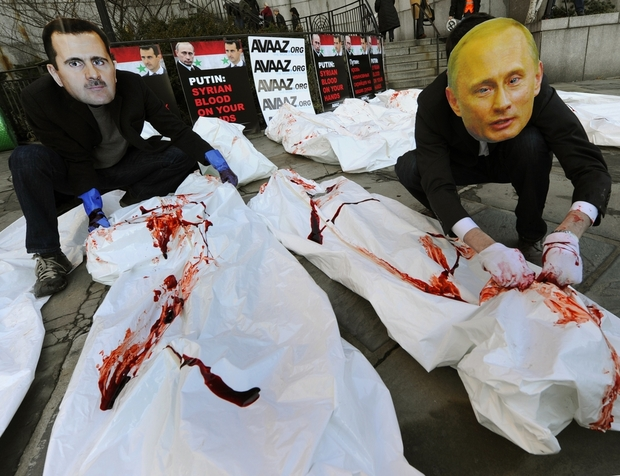 Actors  from Avaaz wearing giant masks of Bashar al-Assad and Vladimir Putin dump dozens of bloodied body bags outside the UN Security Council building January 24,2012  as members of the UN Security Council meet in New York to discuss the Syria crisis, Avaaz will deliver a petition signed by more than 620,000 people worldwide calling for the UN to refer President Bashar al-Assad to the ICC for crimes against humanity.  AFP PHOTO / TIMOTHY A. CLARY